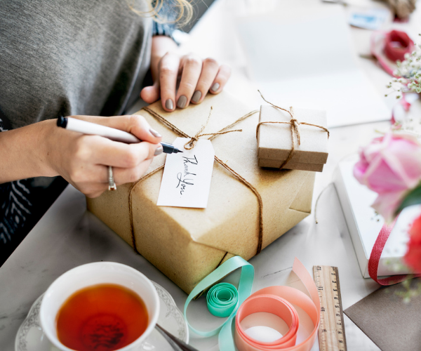 Woman writing thank you message on gift box