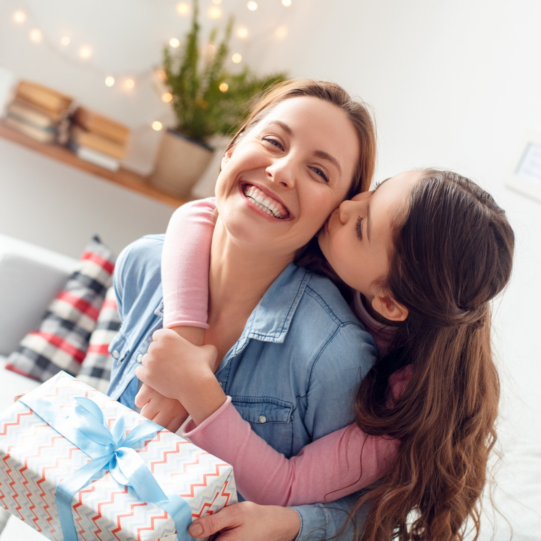 Daughter hugging mum after giving her a gift